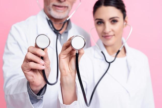 Los doctores están sosteniendo y mostrando los estetoscopios