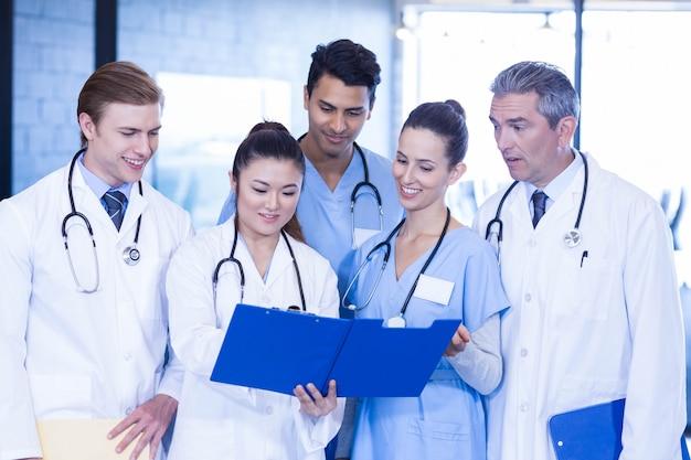 Doctores examinando informe médico en hospital
