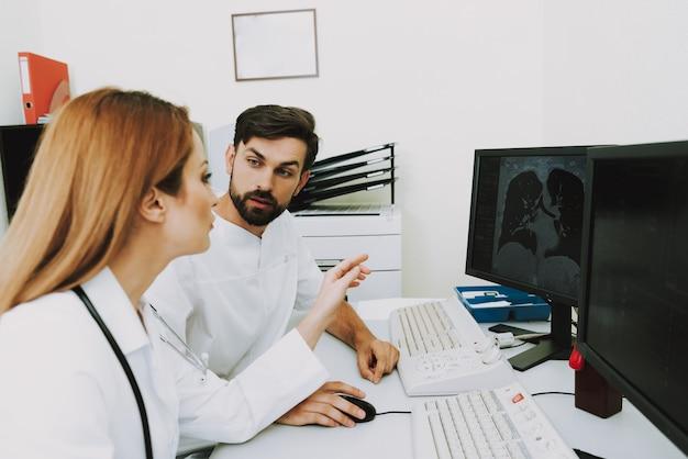 Doctores examinando tomografía computarizada de pulmones discusión.