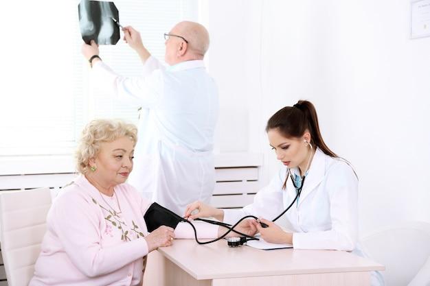 Doctores felices y paciente en la clínica del hospital