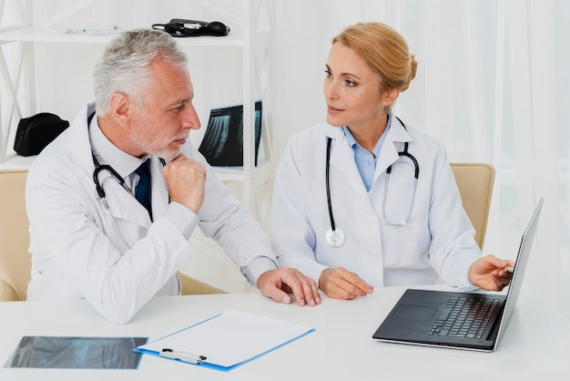 Doctores haciendo investigación en laptop