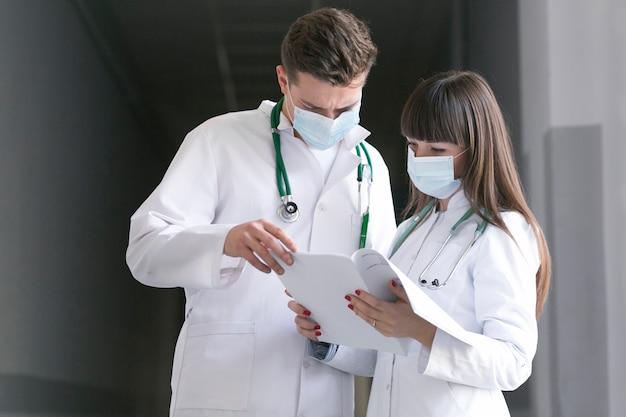Doctores en máscaras con documentos