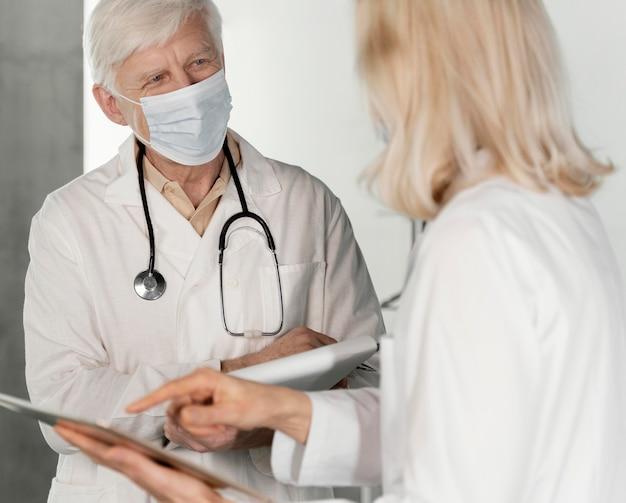 Doctores con máscaras médicas hablando