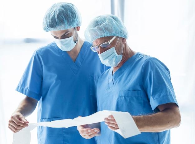 Doctores en máscaras que leen los resultados de las pruebas