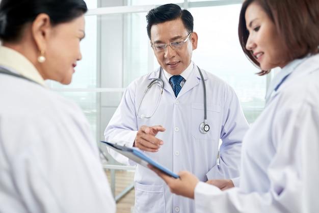 Doctores mayores que ayudan al recién llegado con el diagnóstico