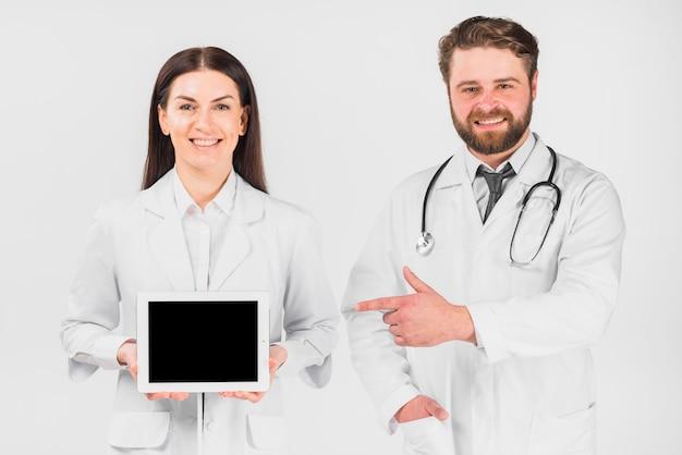 Doctores mujer y hombre mostrando tableta