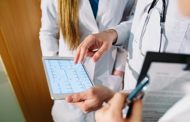 Doctores que discuten el cardiograma del paciente en la tableta.