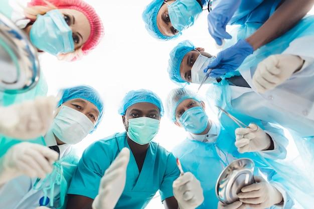 Los doctores que miran fijamente en paciente. mirada de la mesa de operaciones.