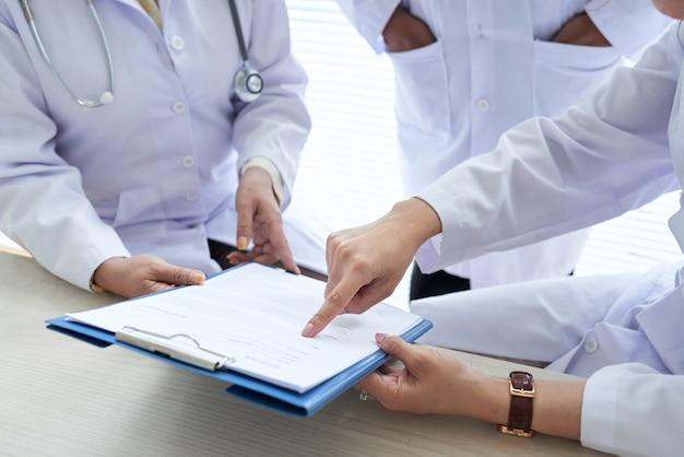 Doctores recortados discutiendo documentos médicos en equipo
