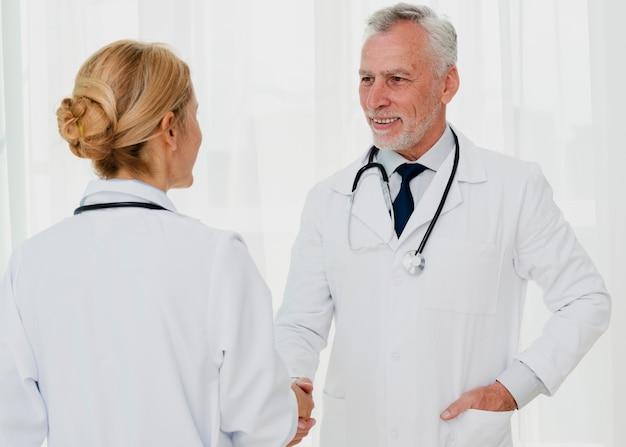 Doctores sonriendo y dándose la mano