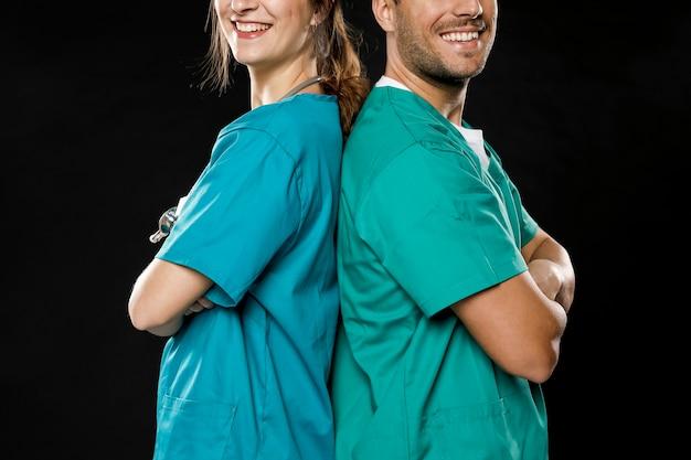 Doctores sonrientes posando espalda con espalda