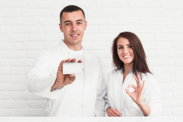 Doctores sonrientes que muestran el signo y la tarjeta de maquetas