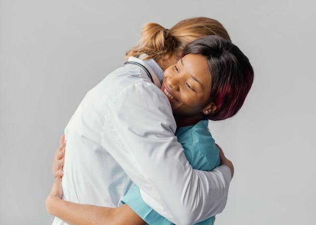 Doctores de tiro medio abrazándose
