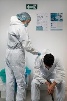 Doctores de tiro medio con traje de materiales peligrosos