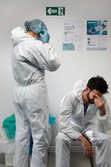 Doctores de tiro medio vistiendo traje de materiales peligrosos