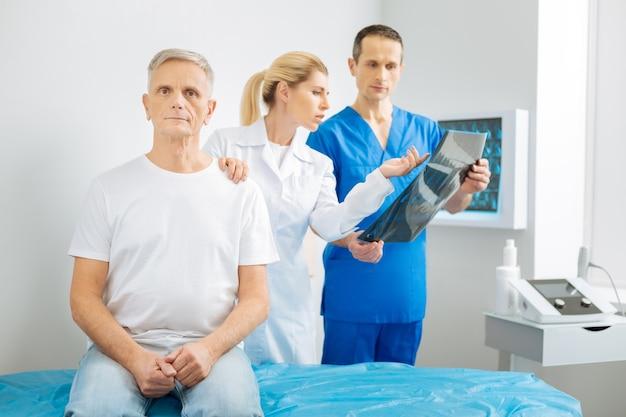 Doctores en el trabajo. inteligente y agradable doctora señalando la foto de rayos x y hablando con su colega mientras agujerea el hombro del paciente
