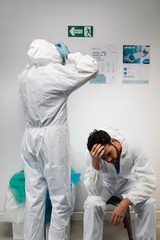 Doctores con traje de materiales peligrosos de tiro medio