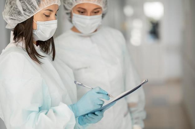 Doctores en trajes de materiales peligrosos en el hospital.