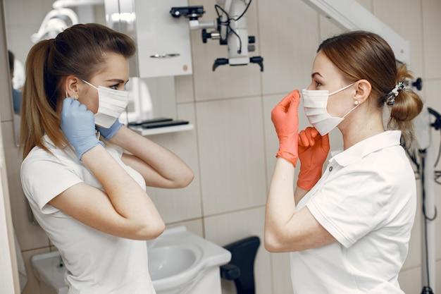 Doctores en uniforme especial los dentistas usan máscaras protectoras las niñas se miran entre sí