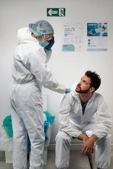 Doctores vistiendo traje de materiales peligrosos tiro medio