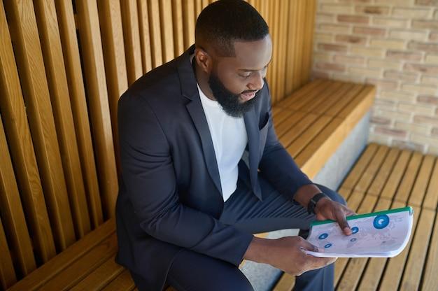 Documentación del proyecto. un hombre de negocios en un traje sentado en un banco con documentos para analizar en las manos
