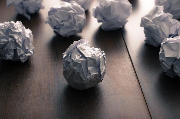 Documento arrugado sobre fondo de madera. frustraciones de negocios, estrés laboral y concepto de examen fallido.