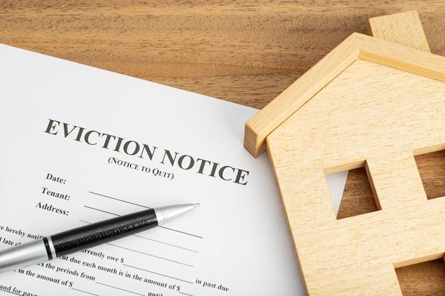 Documento de aviso de desalojo y casa de juguetes en la mesa