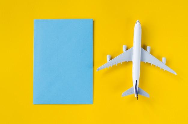 Documento azul vacío sobre fondo amarillo con avión decorativo. concepto de viaje de verano.