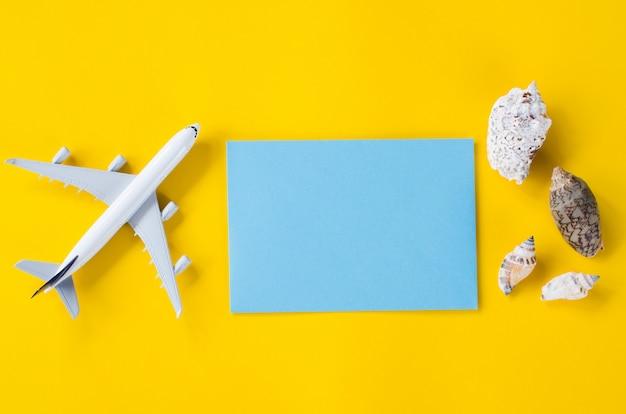 Documento azul vacío sobre fondo amarillo con conchas marinas y avión decorativo. concepto de viaje de verano.