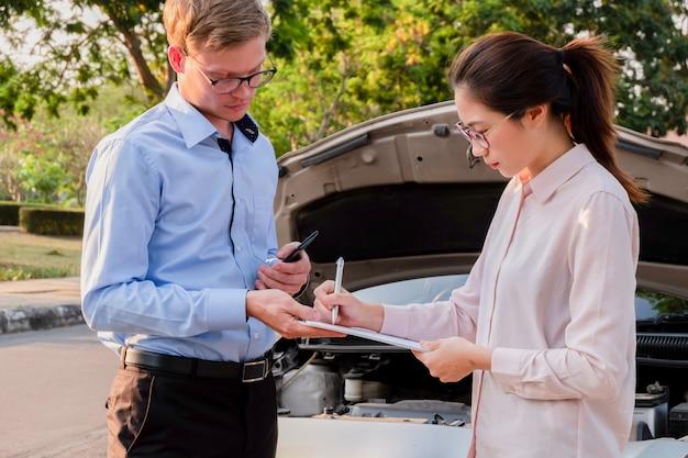 Documento de la escritura del agente de seguros en el portapapeles que examina el coche después del accidente, concepto del seguro