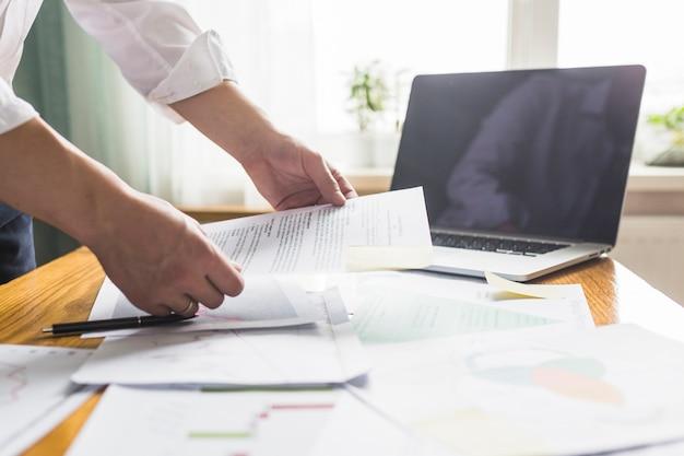 Documento de explotación de la mano del empresario sobre el escritorio de madera