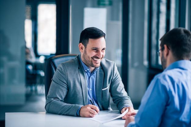 Documento de firma del cliente masculino hermoso en una reunión con el agente inmobiliario.
