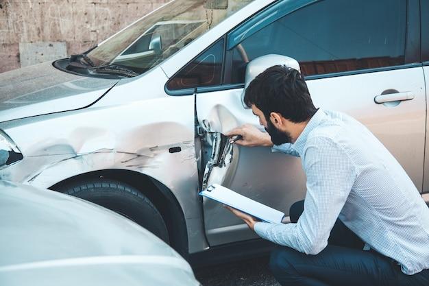 Documento de mano de hombre y accidente de coche
