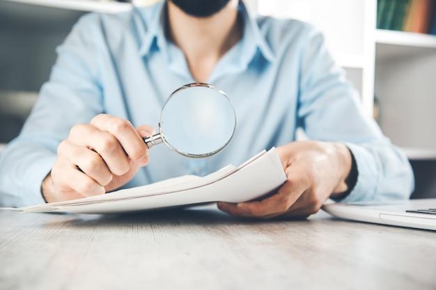 Documento de mano de hombre con lupa en el escritorio