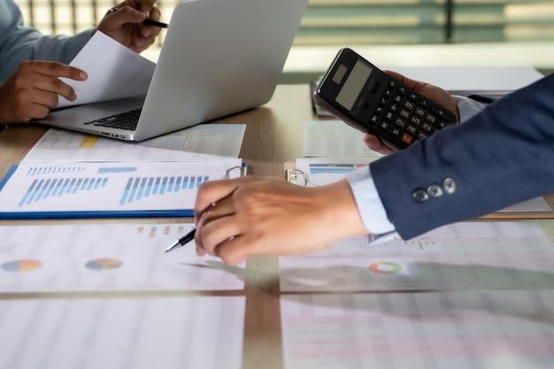 Documentos de análisis contable y hombres de negocios trabajando en ellos.