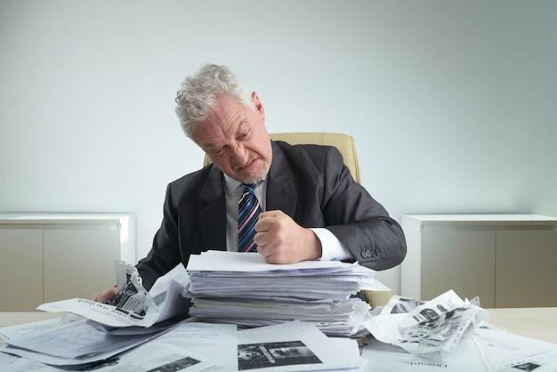 Documentos de arrugamiento del empresario furioso