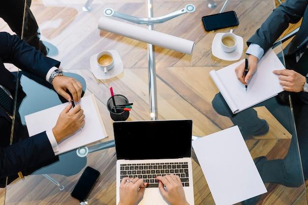 Documentos comerciales en la mesa de oficina con teléfono inteligente y computadora portátil