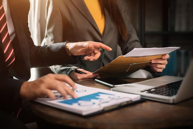 Documentos comerciales en la mesa de la oficina con teléfono inteligente, tableta y computadora portátil y gráfico con diagrama de red social y dos colegas discutiendo datos en la oficina.