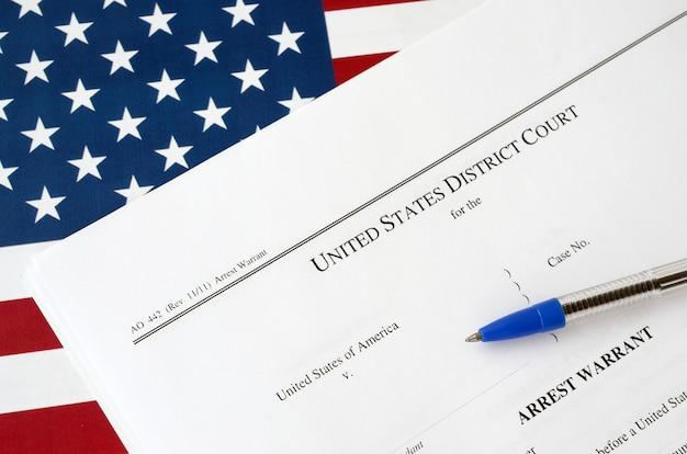 Los documentos de la corte de la orden de detención del tribunal de distrito y la pluma azul en la bandera de los estados unidos permiso para arrestar a un sospechoso