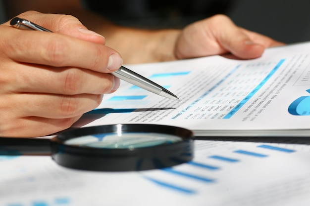 Documentos de estadísticas financieras en el portapapeles en primer plano de la tabla de la oficina