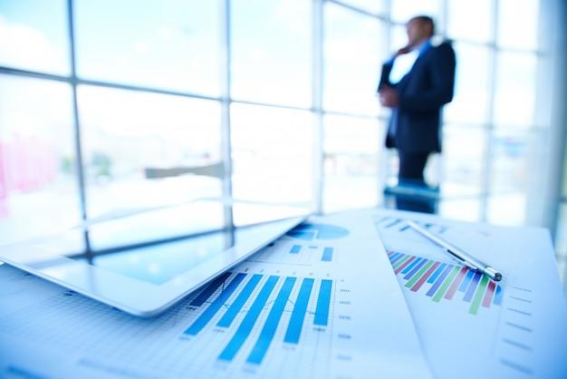 Documentos estadísticos sobre un escritorio con hombre de negocios