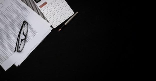 Documentos financieros y calculadoras blancas en escritorios de madera negra.