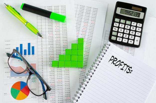 Documentos financieros, con cubos verdes dispuestos en un gráfico de columnas como concepto para aumentar las ganancias