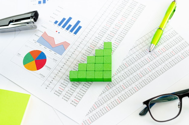Documentos financieros, con cubos verdes dispuestos en un gráfico de columnas como concepto de ingresos, ganancias o ingresos.