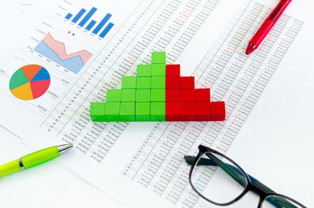 Documentos financieros, con cubos verdes dispuestos en un gráfico de columnas como concepto de ingresos, gastos o flujo de caja.