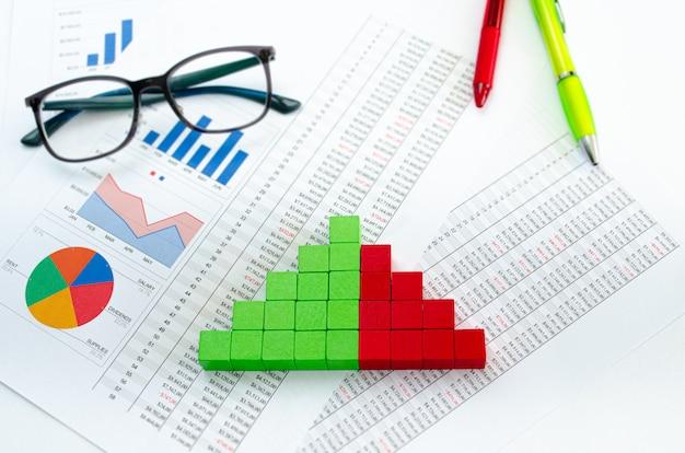Documentos financieros, con cubos verdes dispuestos en un gráfico de columnas como concepto de ingresos, gastos o ganancias.