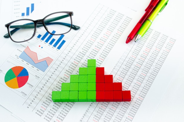 Documentos financieros, con cubos verdes dispuestos en un gráfico de columnas como concepto de ingresos, gastos o ingresos.