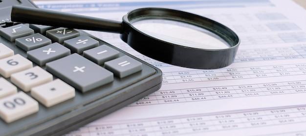 Documentos financieros con lupa sobre ellos.
