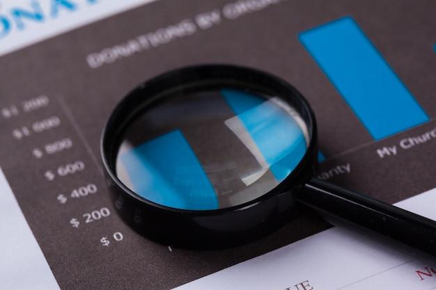 Documentos financieros con lupa sobre ellos