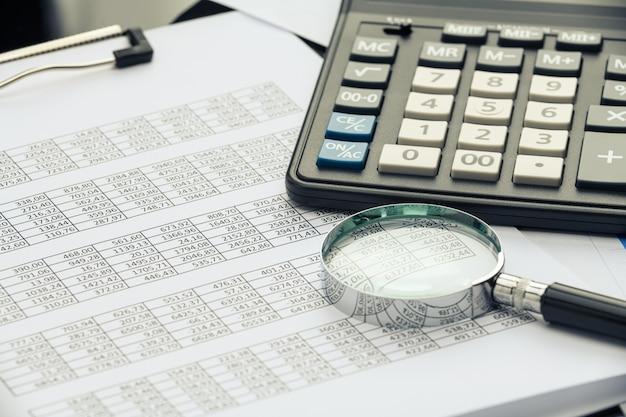Documentos financieros de negocios, calculadora de oficina y lápiz sobre la mesa. números y gráficos